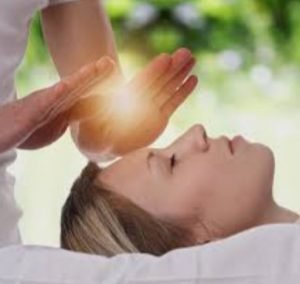 Performing Reiki with hands above head of patient